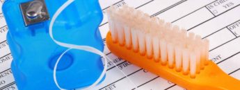 Toothbrush and floss on top of a dental insurance policy