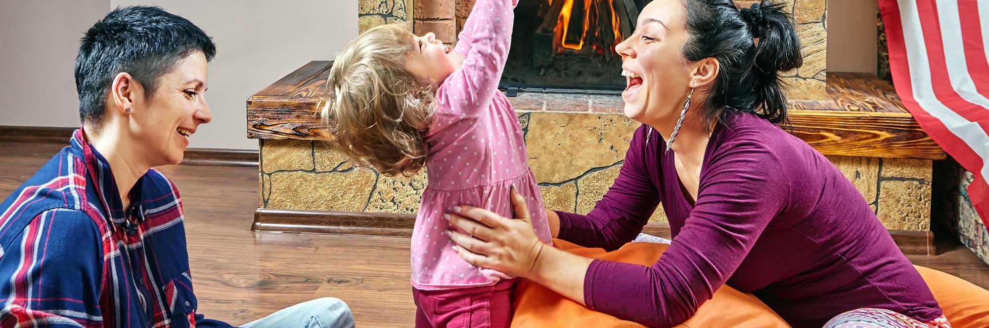 couple playing with child in front of fireplace